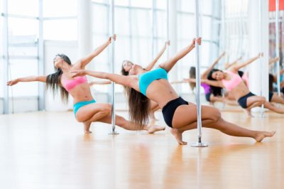 Beautiful women dancing in a pole dance studio